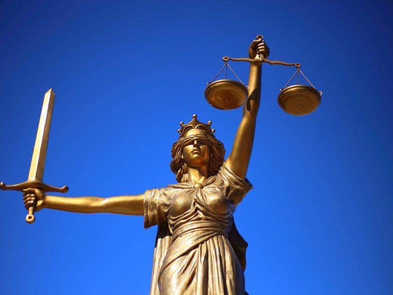 Statue der Justizia vor blauem Himmel
