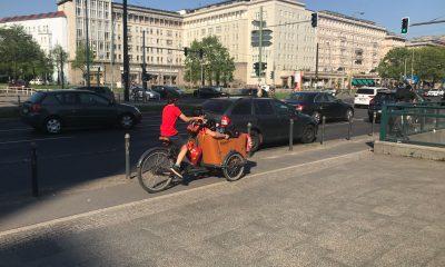 Kind fährt auf Lastenrad über Straße