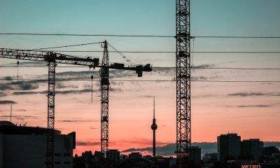 Kräne im Vordergrund einer Berliner Skyline im Sonnenuntergang