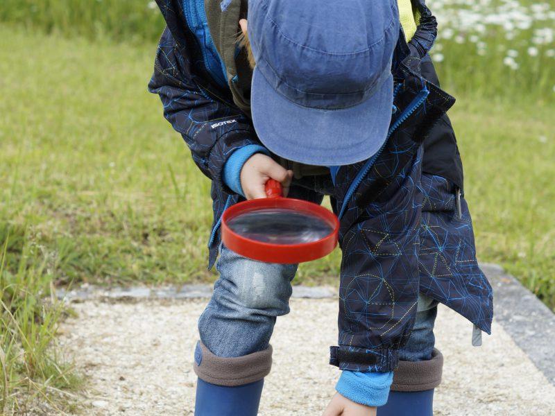 Kind forscht mit einer Lupe in der Natur