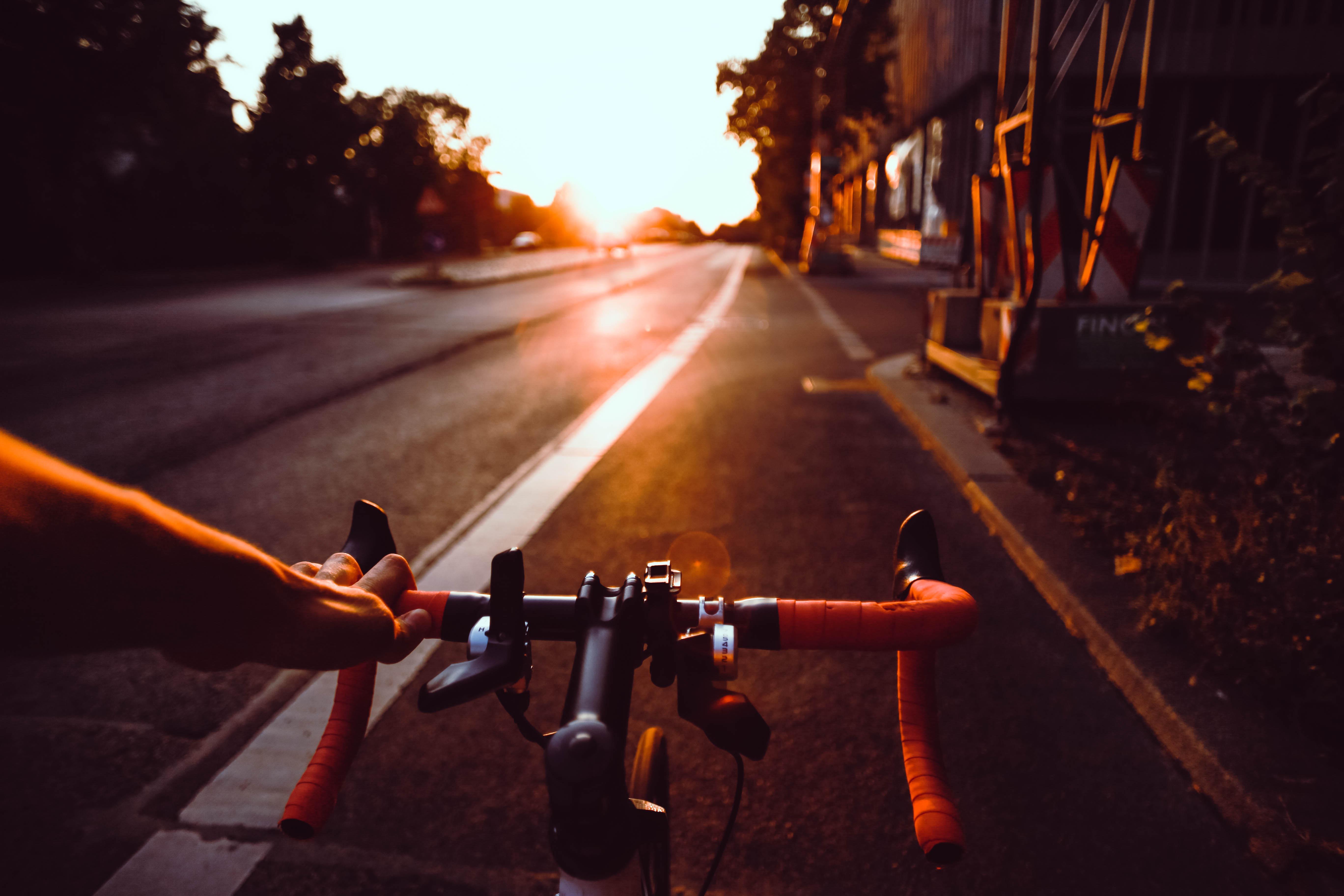 Fahrrad fährt auf der Straße bei Sonnenuntergang