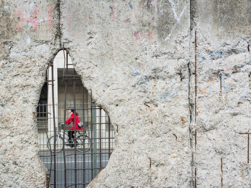 Es ist eine Radfahhrerin durch ein Loch in der Berliner Mauer zu sehen
