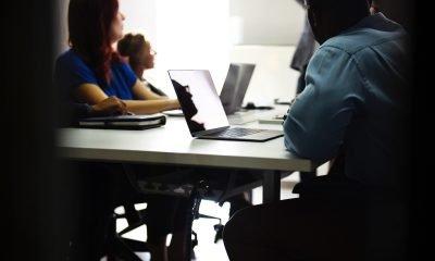 Menschen sitzen gemeinsam an einem Tisch und arbeiten