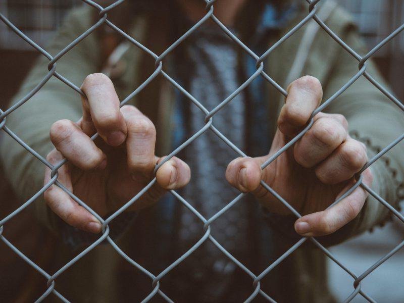 Hände greifen an einen Zaun