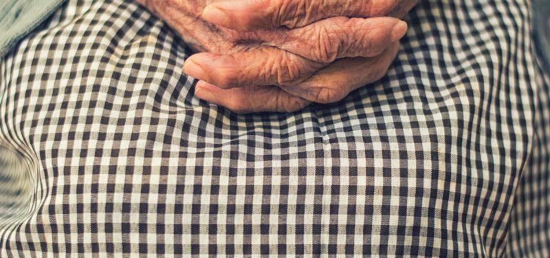Hände einer alten Person liegen gefaltet im Schoß