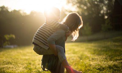 Mädchen trägt einen kleinen Jungen auf dem Rücken