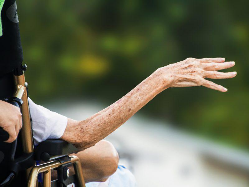 aus einem Rollstuhl gestreckter Arm einer alten Person