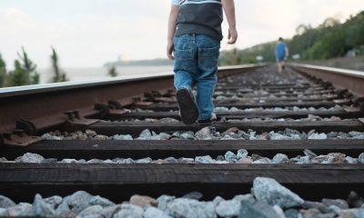 Kind läuft auf Schienen