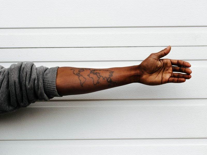 ausgestreckter Arm mit Weltkarte-Tattoo