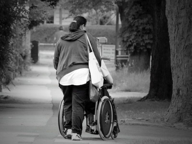 Frau schiebt einen Menschen im Rollstuhl