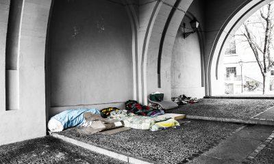 Schlafsäcke, Decken und Kartons liegen in einem Durchgang