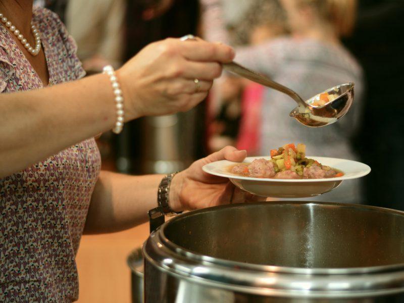 Frau schöpft Suppe aus einem großen Topf in einen Teller