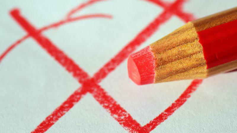 roter Stift mit auf Papier gemaltem Wahlkreuz im Hintergrund