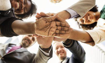 mehrere Menschen halten ihre Hände übereinander