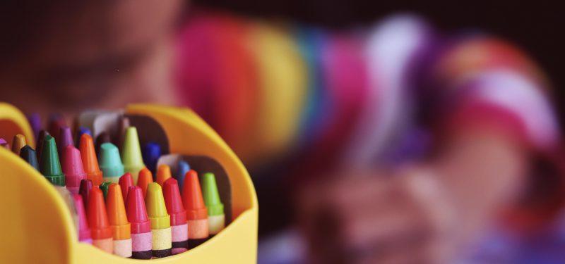 Bunte Stifte mit malendem Kind im Hintergrund