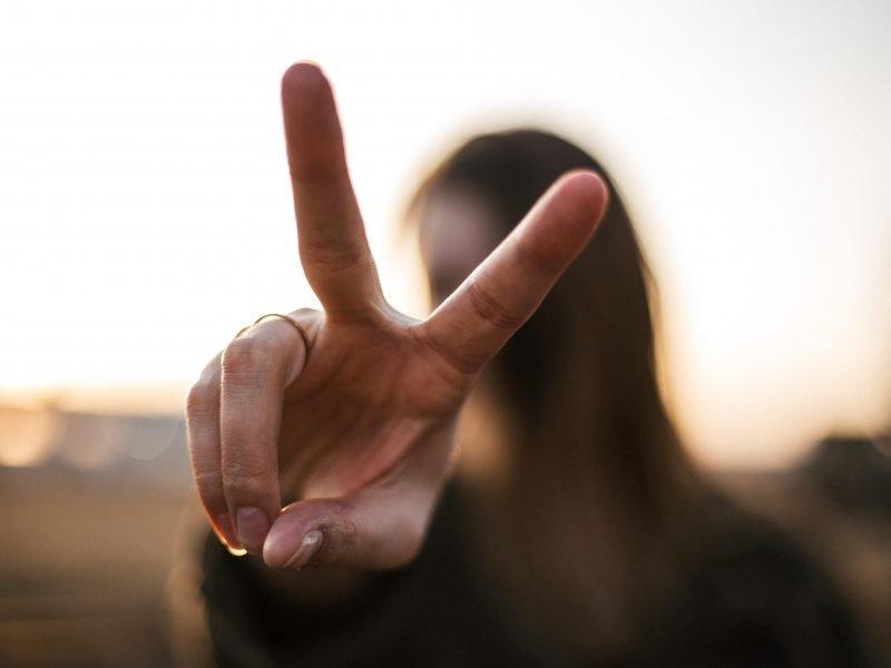 Frau formt mit ihrer Hand ein Victory-Zeichen