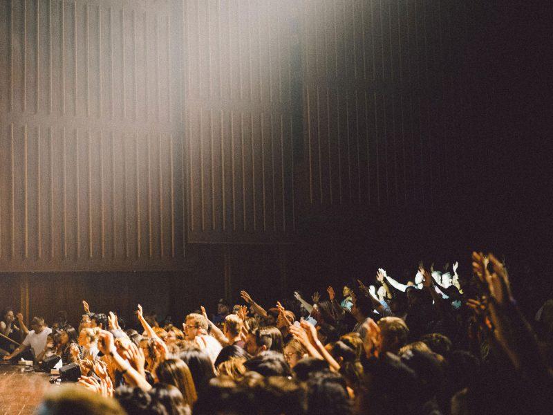 in einem Saal heben viele Menschen ihre Hände in die Höhe
