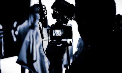 schwarzweiß-Aufnahme eines Mannes mit einer Filmkamera