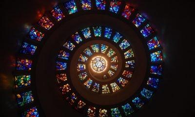 spiralenförmiges buntes Mosaikfenster in dunkler Umgebung