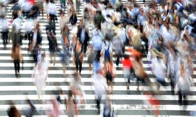 Menschen überqueren schnell eine Straße mit Zebrastreifen