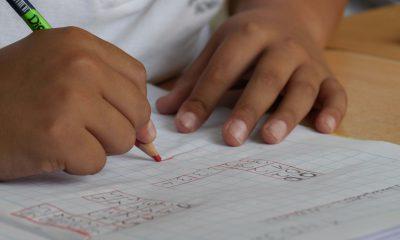 Kinderhand schreibt in ein Heft
