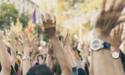 Menschen heben ihre Hände bei einer Demonstration in die Luft