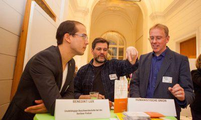 Benedikt Lux diskutiert mit zwei Männern.