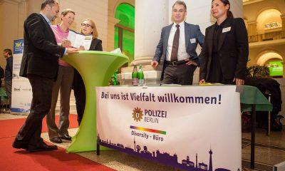 Es sind der Werbetisch der Berliner Polizei und fünf Personen zu sehen.