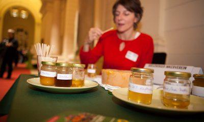 Es ist Honig zu sehen und eine Frau, die im Hintergrund Honig probiert.