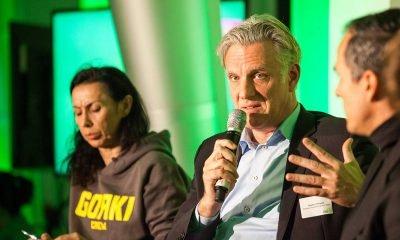 Auf dem Bild ist ein Podiumsteilnehmer zu sehen, der redet und zwei Personen, die ihm zuhören.