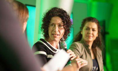 Auf dem Bild ist Bettina Jarasch beim Reden auf einer Podiumsdiskussion zu sehen, die diskutiert.