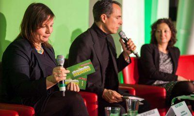 Antje Kapek und Ramona Pop hören einem Mann beim Reden auf dem Podium zu.