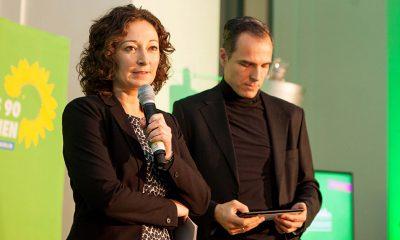 Auf dem Bild ist Ramona Pop zu sehen, während sie auf der Bühne redet. Im Hintergrund steht ein Mann, der auf Moderationskarten schaut.