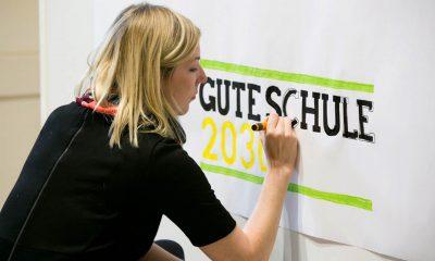 Eine Frau malt ein Plakat.
