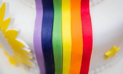 Auf dem Bild ist eine Torte mit Regenbogenverzierung zu sehen.