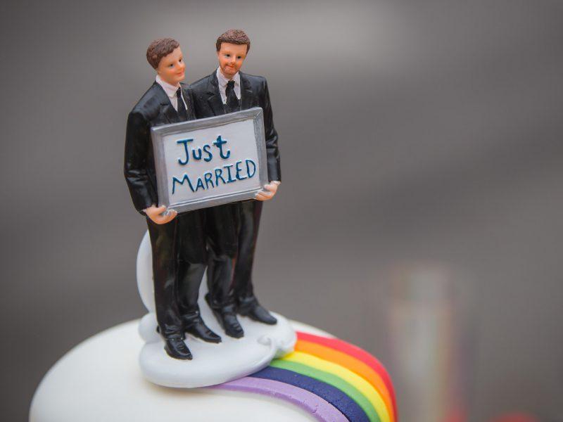 """Auf dem Bild ist die Verzierung einer Torte zu sehen. Zwei Männer aus Zuckerguss halten ein Schild mit der Aufschrift """"Just married""""."""