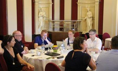 Auf dem Bild sind die Fraktionsvorsitzenden an Tischen zu sehen.