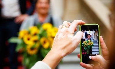 Das Bild zeigt ein Handydisplay, während ein Foto von einer Person gemacht wird.