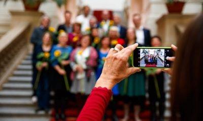Das Bild zeigt ein Handydisplay, während ein Foto von der Gruppe Fraktionsvorsitzenden gemacht wird.