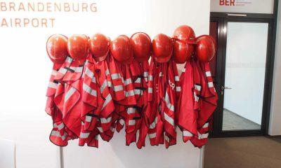 Auf dem Bild sind rote Helme und Arbeitskleidung zu sehen.
