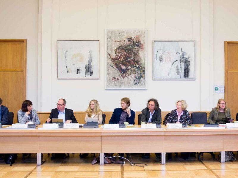 Auf dem Bild sind einige Menschen in einer Sitzreihe während der Klausur zu sehen.