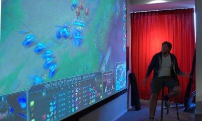 Auf dem Bild ist ein Beamerbild zu sehen, auf dem League of Legends gespielt wird. Ein Mann moderiert das Spiel.