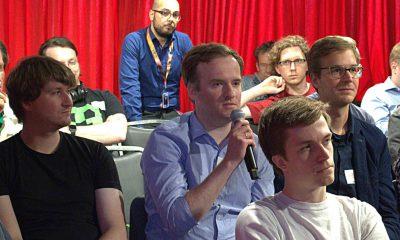 Auf dem Bild ist eine Person zu sehen, die im Publikum redet.