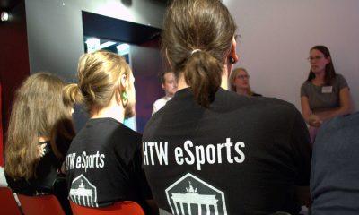 """Auf dem Bild sind mehrere Personen von hinten zu sehen. Zwei haben ein T-Shirt mit der Aufschrift """"HTW eSports"""" an."""