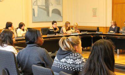 Das Bild zeigt Mädchen, die in einem Sitzungssaal im Kreis sitzen und einige grüne Abgeordnete.