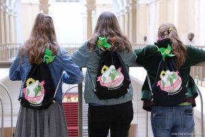 Das Bild zeigt drei Mädchen mit Jutebeuteln von hinten, die im Abgeordnetenhaus stehen.