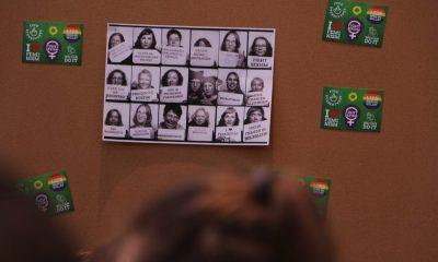 Das Bild zeigt eine Pinnwand mit Fraktionsstickern und ein Bild mit verschiedenen Abgeordneten in schwarz-weiß.