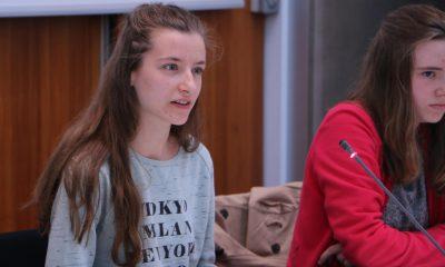 Das Bild zeigt zwei Mädchen, die an einem Sitzungstisch sitzen. Eines der beiden Mädchen redet.