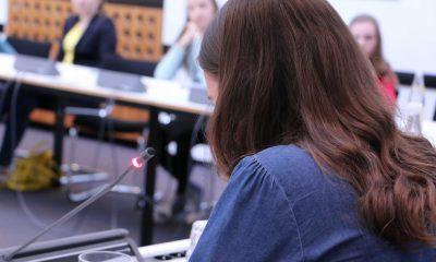 Das Bild zeigt ein Mädchen an einem Sitzungstisch.