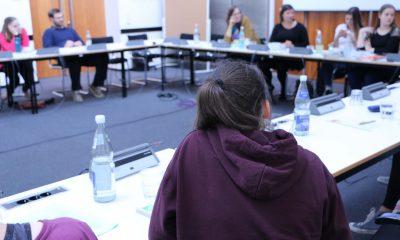 Das Bild zeigt eine Gruppe von Frauen und Mädchen an einem Sitzungstisch.